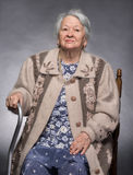 Thoughtful old woman sitting on the chair. On a gray background Royalty Free Stock Photography