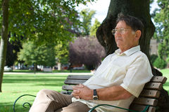 Thoughtful older man. Portrait of a senior older man sitting in a park looking thoughtful Royalty Free Stock Images