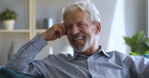 Thoughtful older man looking at camera, hearing good news.