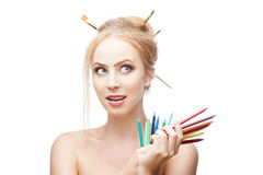 Thoughtful painter girl. Young blond caucasian girl with brushes in hair holding color pencils when looking away with thoughtful expression and smirking Stock Images
