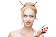 Thoughtful painter girl. Young blond caucasian girl with brushes in hair holding color pencils when looking away with thoughtful expression and smirking royalty free stock photo