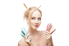 Thoughtful painter girl. Young blond caucasian girl with brushes in hair holding color pencils when looking away with thoughtful expression and smirking Royalty Free Stock Images