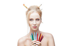 Thoughtful painter girl. Young blond caucasian girl with brushes in hair holding color pencils while looking away with thoughtful expression stock photography