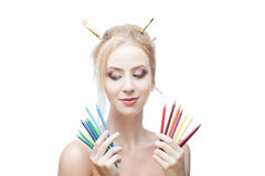 Thoughtful painter girl. Young blond caucasian girl with brushes in hair holding color pencils while looking down with thoughtful expression and smirking Royalty Free Stock Image