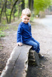 Thoughtful pensive little boy sitting on a wooden bench in a par Royalty Free Stock Images