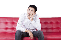 Thoughtful person sitting on couch Royalty Free Stock Photo