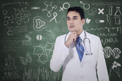 Thoughtful physician with doodle on blackboard Royalty Free Stock Photo