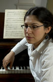 Thoughtful Piano Teacher. Pensive portrait of a piano teacher sitting in profile in front of a piano, with music open on the piano stand.  Teacher seated to far Stock Photography