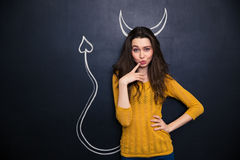 Thoughtful playful young woman standing over chalkboard background Royalty Free Stock Photos
