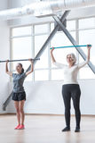 Thoughtful pleasant women holding gymnastic sticks Stock Photo