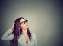 Thoughtful pondering woman in eyeglasses scratching head perplexed royalty free stock image
