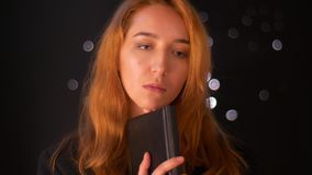 Thoughtful position of caucasian ginger female close up standing and looking aside dissolved in her minds and holding. Black book near her face, dark background stock video footage