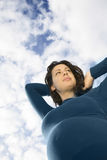 Thoughtful Pregnant Woman Against Clouds Stock Photography