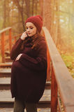 Thoughtful pregnant woman in soft warm cozy marsala outfit walking outdoors Stock Photos