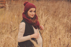 Thoughtful pregnant woman in soft warm cozy outfit walking outdoors Royalty Free Stock Photo