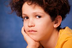 Thoughtful preteen boy looking at camera. Close-up portrait of thoughtful preteen boy looking at camera Stock Photo