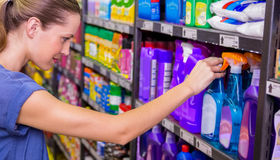 Thoughtful pretty brunette looking at product in shelf Stock Photography