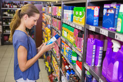 Thoughtful pretty brunette looking at product in shelf Royalty Free Stock Photo