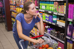 Thoughtful pretty brunette pushing trolley Royalty Free Stock Photo