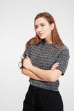 Thoughtful pretty businesswoman standing with hands folded and thinking Stock Photos