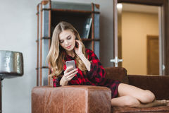 Thoughtful pretty girl in plaid shirt using cellphone Royalty Free Stock Images