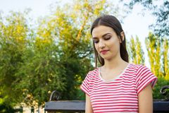 Thoughtful pretty girl sitting alone outdoors in the park Stock Image