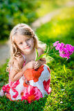 Thoughtful pretty little girl squatting and holding purple flowe Stock Image