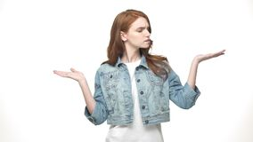Thoughtful pretty redheaded woman present hand on side and hard to choose while standing isolated over white background.  stock video footage