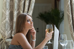 Thoughtful pretty woman posing with glass of wine Royalty Free Stock Photos