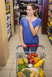 Thoughtful pretty woman pushing trolley in aisle Stock Photo