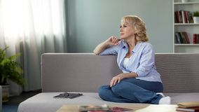 Thoughtful pretty woman relaxing on sofa at home, free time retirement, leisure. Stock photo stock images