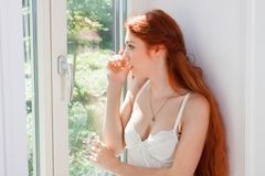 Thoughtful Pretty Woman Sitting at the Window Royalty Free Stock Image