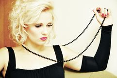 Thoughtful pretty woman with string of black beads Royalty Free Stock Photo
