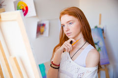 Thoughtful pretty young redhead woman artist thinking and making sketches Stock Photography