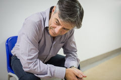 Thoughtful professor sitting on chair. In corridor Stock Images