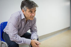 Thoughtful professor sitting on chair stock photos
