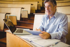 Thoughtful professor using digital tablet Royalty Free Stock Images