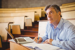 Thoughtful professor writing in book at desk Royalty Free Stock Images
