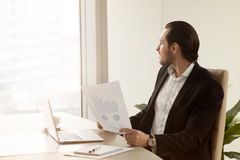 Thoughtful project manager in office is holding financial report Stock Photo