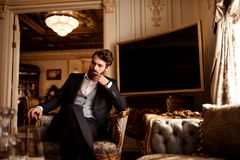 Thoughtful prosperous male involved in business, dressed in formal suit, sits in royal room on comfortable chair, waits. For partner, has pensive expression Stock Photography
