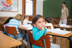 Thoughtful pupil sitting at her desk Royalty Free Stock Images