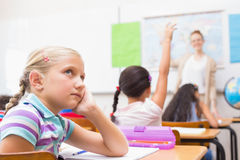 Thoughtful pupil sitting at her desk Stock Photography