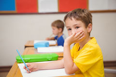 Thoughtful pupil sitting at his desk Stock Images