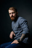 Thoughtful red bearded man studio portrait on dark background Royalty Free Stock Images
