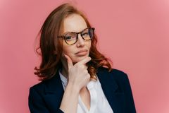 Thoughtful red haired lady holds chin, looks with contemplative expression at camera, thinks over future plans, has full lips,. Healthy skin, dressed in formal royalty free stock photography