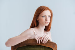 Thoughtful redhead woman sitting on the chair Royalty Free Stock Images