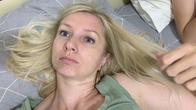 Thoughtful relaxed blond woman lying in bed and touching, stroking her hair.  stock video footage