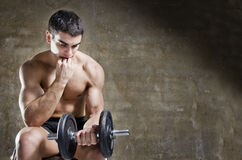 Thoughtful and relaxed man training with dumbbell Royalty Free Stock Photos