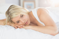 Thoughtful relaxed woman lying in bed Stock Images