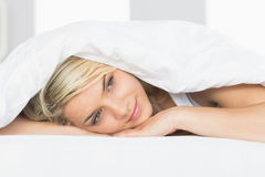 Thoughtful relaxed woman lying in bed Stock Photo